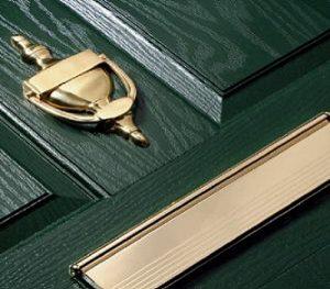 dark green composite front door with brass furniture